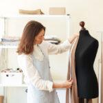 brunette-seamstress-apron-measuring-beautiful-fabric-black-dummy-workshop_171337-7341