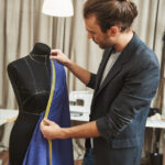 vertical-portrait-adult-good-looking-caucasian-male-fashion-designer-with-stylish-hairstyle-fashionable-outfit-his-studio-working-new-dress-winter-clothes-collection_176420-11850